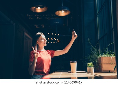 Attractive nice smiling young girl wearing casual sitting in cafeteria, making selfie, showing v-sign, drinking coffee, dark interior