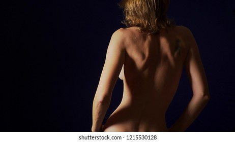 Attractive nude woman in white panties, covering her breasts with her hands. Black background