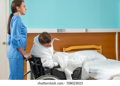 Attractive nurse in uniform pulling wheelchair with ill patient covered with quilt in hospital ward. Healthcare concept