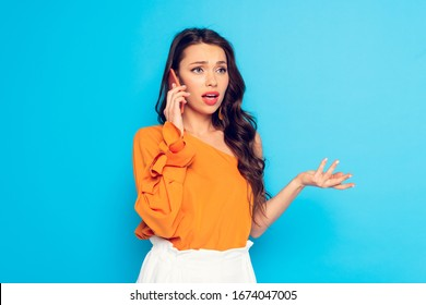 attractive, offended girl talking on smartphone while standing with open arm isolated on blue