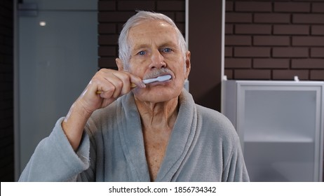 Attractive old senior man grandfather in bathrobe brushing teeth looking into mirror. Handsome elderly grandpa doing morning hygiene after shower at luxury bathroom at home. Point of view. POV shot