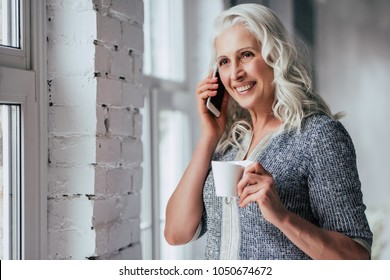 Attractive old woman at home. Senior smiling lady is sitting on a sofa with smart phone in hands while drinking tea.