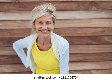 Attractive older blond woman with a vivacious smile standing in front of a wooden wall leaning forwards staring into the camera
