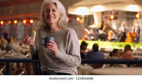 Attractive older woman in cafe listening to band playing on stage snaps fingers