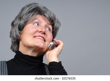 Attractive older woman chatting on the phone with copy space to the right