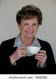 Attractive older woman drinking coffee or tea.