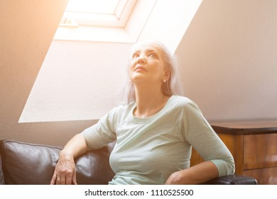 Attractive older woman enjoying the warmth of the sun as she relaxes on a sofa under a skylight window looking up with flare
