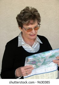 Attractive older woman reading a map.
