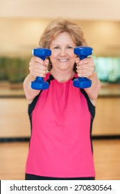 An attractive older woman smiles as she holds hand weights straight out towards the camera in an exercise studio.  The plastic-coated blue dumbbells are in sharp focus, and the woman is in background.