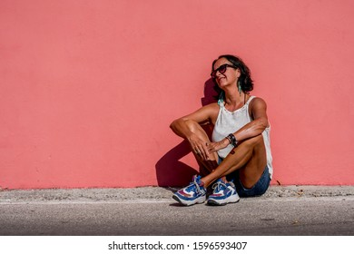 Attractive older woman with suntan wearing sunglasses leaning against a bright light pink monochrome wall. Sunny sunshine day one person older mature female.
