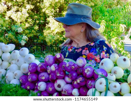 48bab16f4830 Attractive older woman wearing a hat and sunglasses making health choices  at a farmer s market