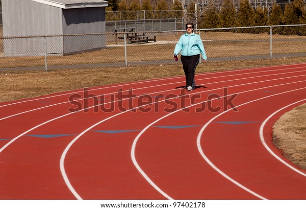 Attractive overweight woman walking around the high school track