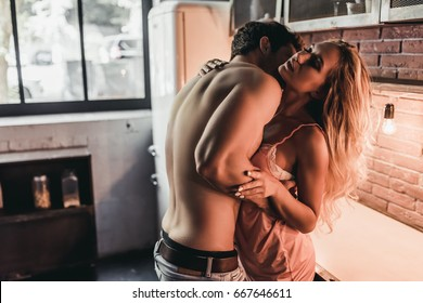 Attractive passionate couple is having sex on kitchen.