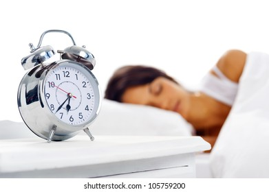 Attractive peaceful sleeping dreaming latino woman in bed with alarm clock