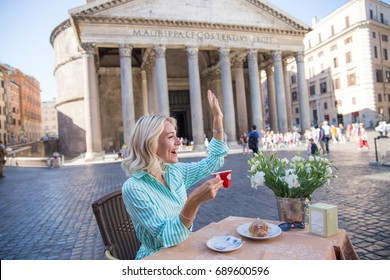 attractive pensive blond woman drinking italian coffee in the morning and seeting in a street cafe in Rome