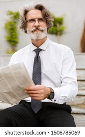 Attractive pensive mature bearded businessman holding newspaper while sitting outdoors and looking away