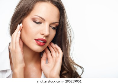 Attractive pensive woman is touching her face thoughtfully.  She is looking down with sadness. Isolated on background and copy space in right side