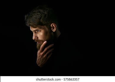 Attractive pensive young man looks into the distance stroking his beard over black background