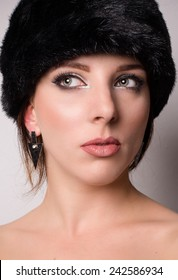 Attractive pensive young woman with bare shoulders in a winter hat looking off to the side with her eyes with a thoughtful expression