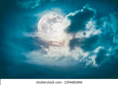 Attractive photo of cloudscape at nighttime. Night landscape of sky with bright full moon behind clouds, serenity nature background.  The moon taken with my own camera.