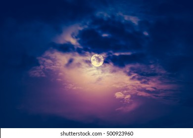 Attractive photo of a nighttime sky with dark cloudy and bright full moon. Full moon behind clouds at night. Vintage effect tone. The moon were NOT furnished by NASA.