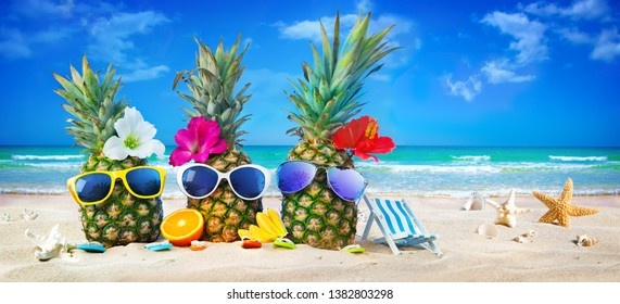 Attractive pineapples in stylish sunglasses on the sand beach against turquoise sea. Tropical summer vacation concept
