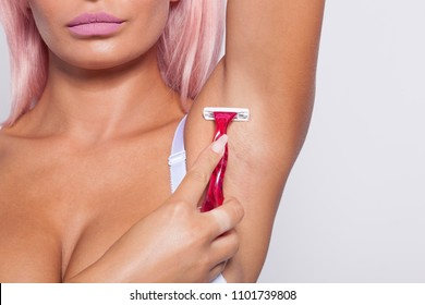 Attractive pink hair young woman gently shaving armpit epilation hair removal with ergonomic pink shaver. Body care skincare beauty concept