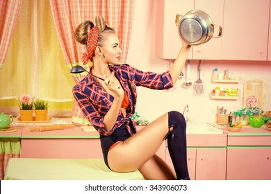 Attractive pin-up girl cooking on her pink kitchen. Retro style. Fashion.