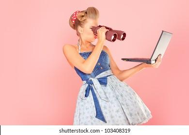 Attractive pin-up girl looking through binoculars to her laptop.