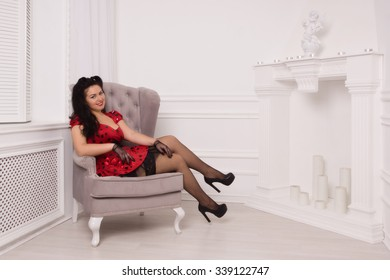 Attractive pin-up girl sitting on a chair in in the vintage interior