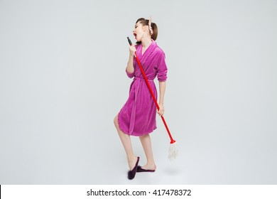 Attractive playful young housewife singing and dancing with mop