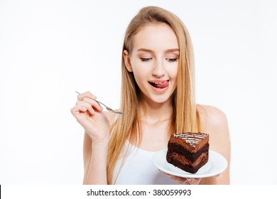 Attractive playful young woman holding and eating piece of chocolate cake over white background