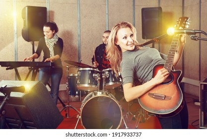 Attractive pleasant cheerful female soloist playing guitar and singing with her music band in sound studio