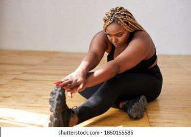 attractive plus size afro american female stretching legs on the floor sit alone doing exercises. isolated in studio