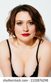 Attractive plus size model with bright makeup wearing black bra and looking at camera on white background