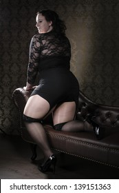 Attractive plus size model wearing black lace lingerie, lying an a brown chesterfield sofa.