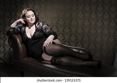 Attraktives und größenmäßiges Modell mit schwarzer Spitzen-Dessous und einem braunen Chesterfield-Sofa.