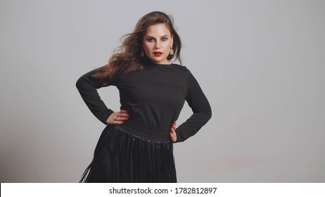 Attractive plus-size busty woman with stylish make-up and clothes standing isolated. Studio shot of elegant oversize model with nose piercing posing for camera. Body positive and fashion portrait