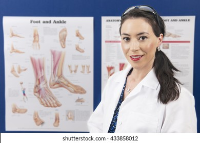 An attractive podiatrist happily looking at the viewer as she stands in front of her education charts.