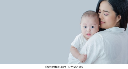 Attractive Portrait Asian mother carrying baby boy with copy space panoramic banner,Happy asian family healthcare love together with kid,mother's day concept
