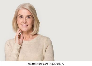 Attractive positive blonde mature woman thinking posing aside on isolated grey studio background, copy space aesthetic medicine offer, anti aging health beauty procedure ad, medical insurance concept