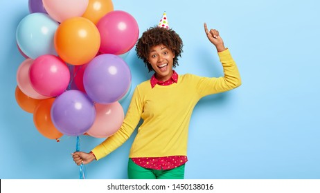 Attractive positive dark skinned woman carries multicolored birthday balloons, laughs and points upwards, wears cone hat, fashionable clothes, prepares for having holiday. Celebration and fun
