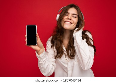 Attractive positive young brunette curly woman wearing white shirt isolated on red background wall holding and showing mobile phone with empty display wearing white bluetooth headphones listening to