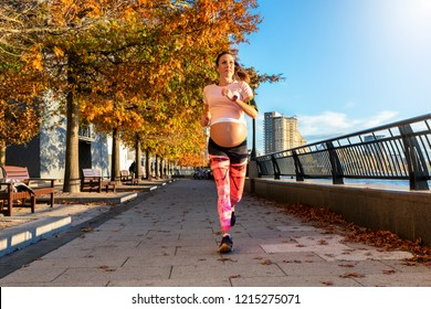Attractive, pregnant woman running outdoors in the autumn city at the riverside in London