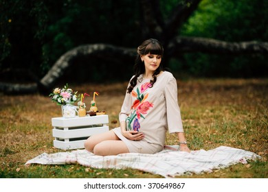 Attractive pregnant woman  is sitting with her hand on belly on checkered blanket in the autumn park on picnic.