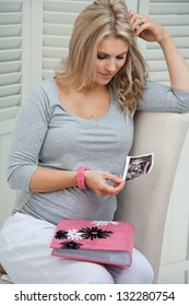 Attractive pregnant woman sitting at home on chair holding ultrasound scan of baby, smiling and holding pink family photo album