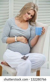 Attractive pregnant woman sitting at home on chair holding blue mug, smiling and touching her tummy