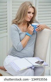 Attractive pregnant woman sitting at home on chair holding blue mug
