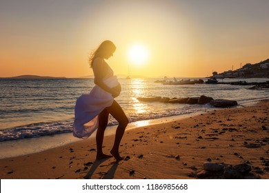 Attractive, pregnant woman stands on the beach and holds her belly during sunset time