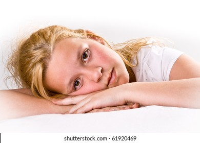 Attractive pre-teen girl looking intensely at viewer, laying down